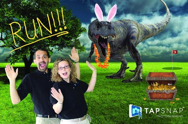Mark and Emily Radel, owners of TapSnap 1129 photo booth rentals, in front of a T-Rex TapSnap green screen