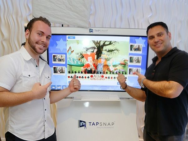 Michael Rozen, owner of TapSnap 1153, shows off his kiosk with a member of his event entertainment team.