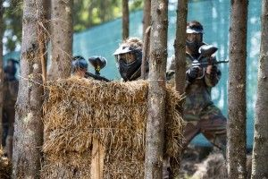 group of people playing paintball, hiding behind a bundle of straw
