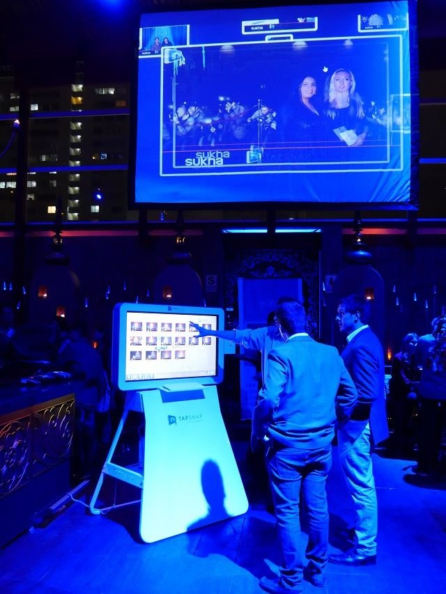 Three men playing with the TapSnap photo booth. Above them is a projection screen displaying an event photo through SnapCast