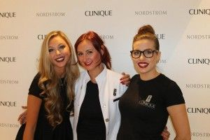 Three ladies standing in front of a step and repeat for Clinique, and smiling