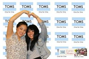 Two girls posing in front of a step and repeat for TOMS
