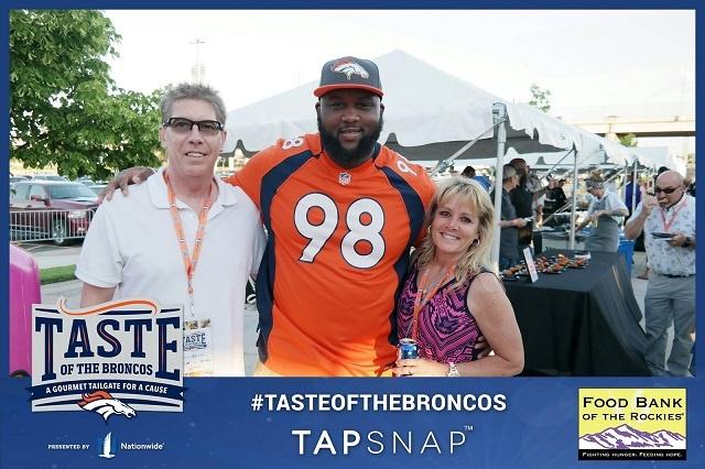 NFL fans pose with Denver Broncos player, Darius Kilgo.