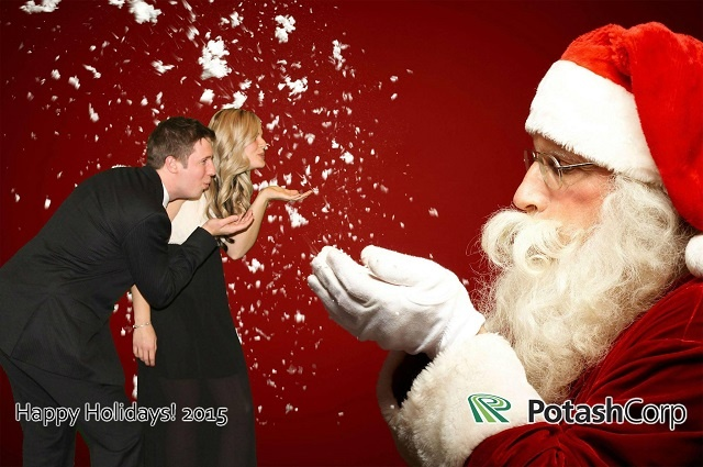Couple against a green screen background of Santa blowing snow from his hands