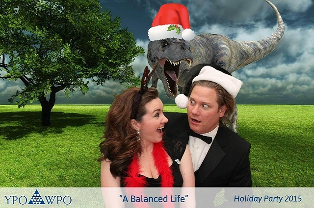 A couple standing against a green screen background of a T-Rex wearing a Santa hat