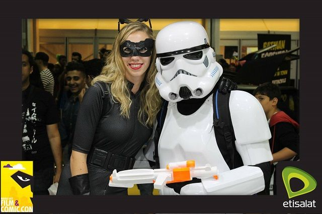 People dressed as cat woman and a storm trooper in photo booth picture from comic con